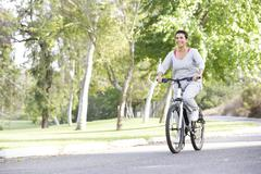 Senior woman cycling in park Stock Photos