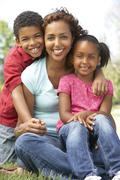 Mother With Children In Park Stock Photos