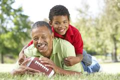Grandfather With Grandson In Park With American Football Stock Photos