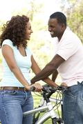 Couple On Cycle Ride in Park - stock photo