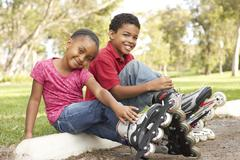 Children Putting On In Line Skates In Park Stock Photos