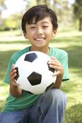 Portrait Of Young Boy In Park With Football - stock photo