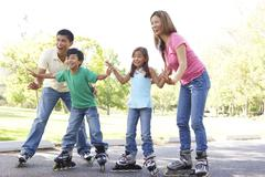 Family  Skating In Park on In Line Skates Stock Photos