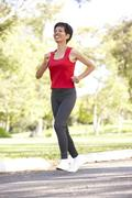 Senior Woman Jogging In Park - stock photo