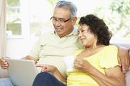 Stock Photo of Senior Couple Using Laptop At Home