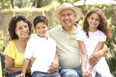 Portrait Of Grandparents With Grandchildren In Park Stock Photos