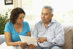 Stock Photo of Senior Couple Studying Financial Document At Home