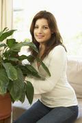 Nainen kotona huolehtiminen huonekasvi Kuvituskuvat