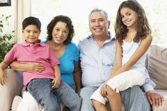Grandparents With Grandchildren Relaxing At Home Together Stock Photos