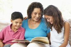 Grandmother Reading With Grandchildren At Home Together - stock photo