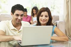 Parents Using Laptop At Home - stock photo