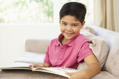 Young Boy Reading Book At Home - stock photo