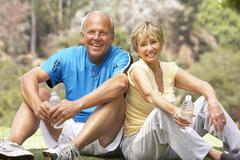 Senior Couple Resting Aftre Exercising In Park Stock Photos
