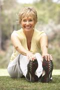 Senior Woman Exercising In Park Stock Photos