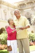 Senior Couple Walking Through City Street With Map Stock Photos