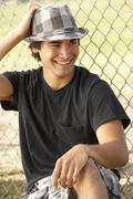 Teenage Boy Sitting In Playground Wearing Hat Stock Photos
