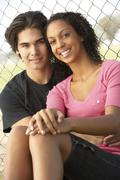 Teenage Couple Sitting In Playground Stock Photos