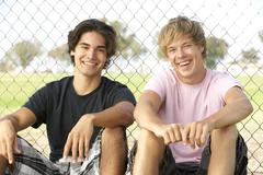 Teenage Boys Sitting In Playground - stock photo