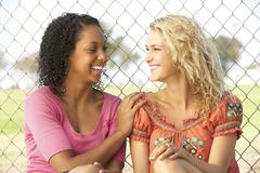Teenage Girls Sitting Together In Playground Stock Photos