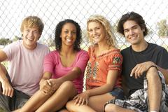 Group Of Teenagers Sitting In Playground Stock Photos