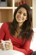Young Woman Sitting On Sofa With Cup Of Coffee - stock photo