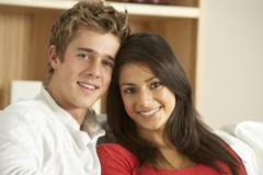 Young Couple Sitting On Sofa - stock photo