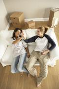Stock Photo of Girlfriends Moving Into New Home