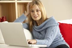 Young Woman Sitting On Sofa Using Laptop Stock Photos