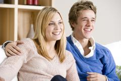 Young Couple Sitting On Sofa Together Watching TV - stock photo