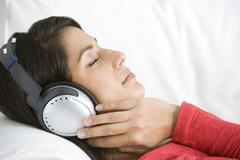 Woman Relaxing Listening To Music Wearing Headphones - stock photo