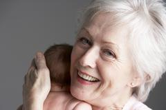 Studio Shot Of Grandmother Cuddling Granddaughter - stock photo