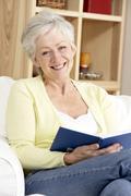 Senior Woman Reading Book At Home - stock photo