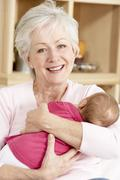 Grandmother Cuddling Granddaughter At Home - stock photo