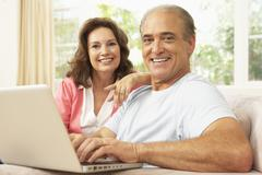 Senior Couple Using Laptop At Home Stock Photos
