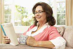 Senior Woman Reading Book With Drink At Home Stock Photos