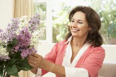 Senior Woman At Home Arranging Flowers Stock Photos