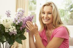Woman At Home Arranging Flowers Stock Photos