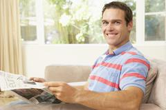 Man Reading Newspaper At Home - stock photo