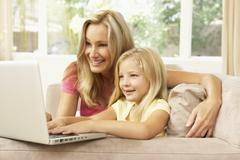 Mother And Daughter Using Laptop At Home - stock photo