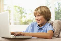 Young Girl Using Laptop At Home Stock Photos
