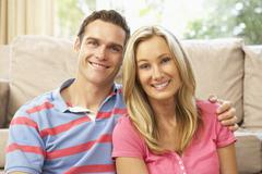 Young Couple Relaxing On Sofa At Home Stock Photos