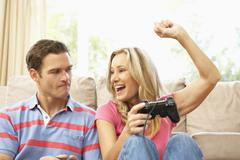Young Couple Playing Computer Game On Sofa At Home Stock Photos