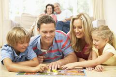 Family Playing Board Game At Home With Grandparents Watching Stock Photos