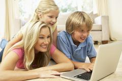 Mother And Children Using Laptop At Home Stock Photos