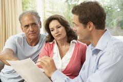 Senior Couple With Financial Advisor At Home - stock photo