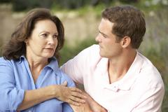 Senior Woman Being Comforted By Adult Son - stock photo