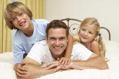 Father And Children Relaxing On Bed At Home - stock photo