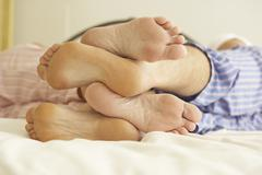 Close Up Of Couple's Feet Relaxing On Bed At Home Stock Photos