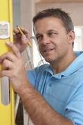 Builder Using Spirit Level On Wall - stock photo