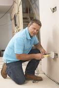 Electrician Installing Wall Socket - stock photo